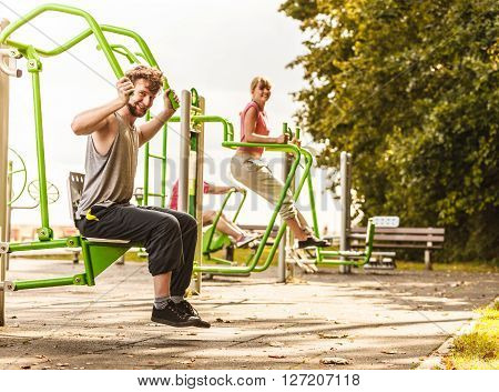 Active Man And Woman Exercising At Outdoor Gym.