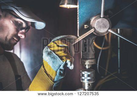 Drill Works in a Garage. Caucasian Men Using Metal Driller.