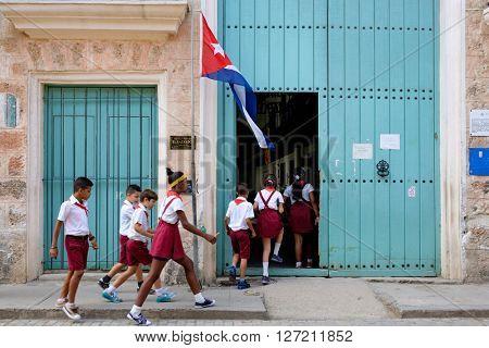 HAVANA,CUBA - APRIL 20,2016 : A group of uniformed cuban children entering a primary school in Old Havana
