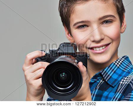 Boy with photo camera taking pictures. Portrait of the caucasian boy  with digital camera in hands