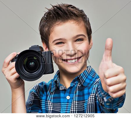 Boy with camera taking pictures. Happy fun boy  with dslr camera showing the thumb up