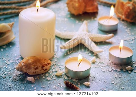 Burning candles on a background of sea objects tinted.
