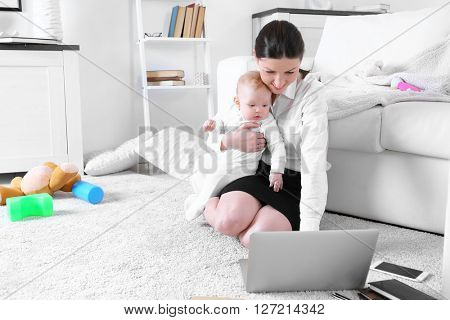 Businesswoman with baby boy working from home using laptop