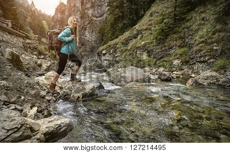Woman hiking around mountains near the river at spreeng time.