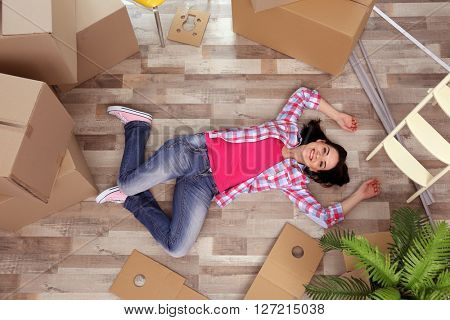 Young woman moving in new house. Top view.