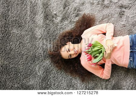 Young woman on the carpet holding tulips