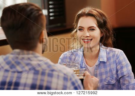 Happy young couple dating in pub