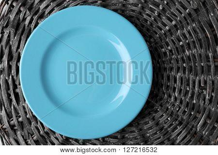 Empty plate on wicker mat background