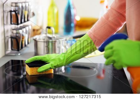 Human hand in protective gloves washing electric hob in the kitchen