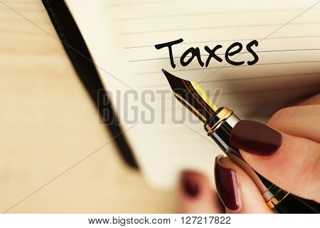 Tax Concept. Female hand writing TAXES by pen on wooden table background