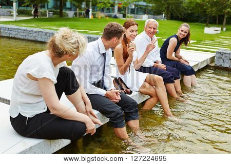 Business team in summer cooling their feet in water during a meeting