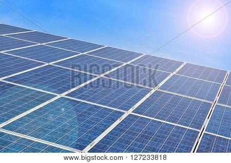 Solar panel with bright sun on blue sky