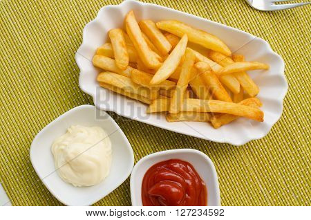 French fries on a white plate with tomato sauce and mayonnaise