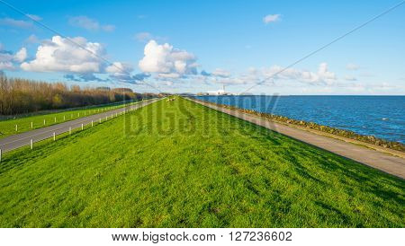 Dike along a lake in spring below a blue cloudy sky