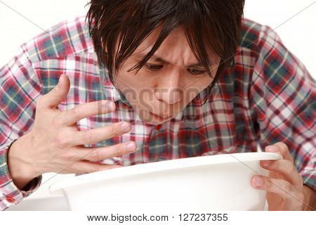 portrait of young Japanese man feels like vomiting on white background