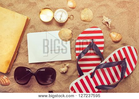 Beach summer holiday vacation accessories on sandy beach, top view arrangement.