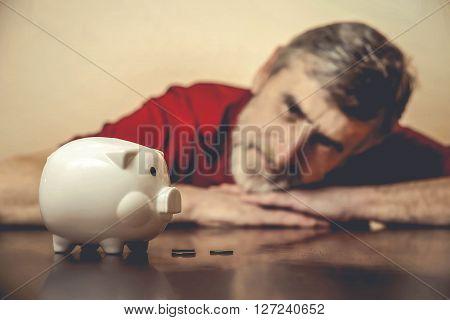 Senior man sadly looking at piggy bank