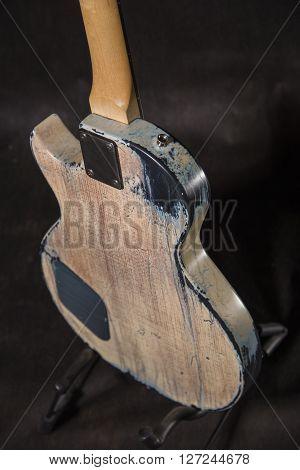 Aged guitar back on a black background