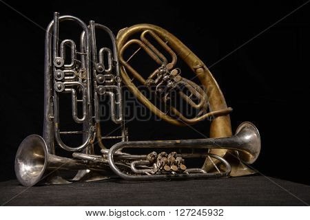 Four old brass wind instrument and horn stand on a table on a black background