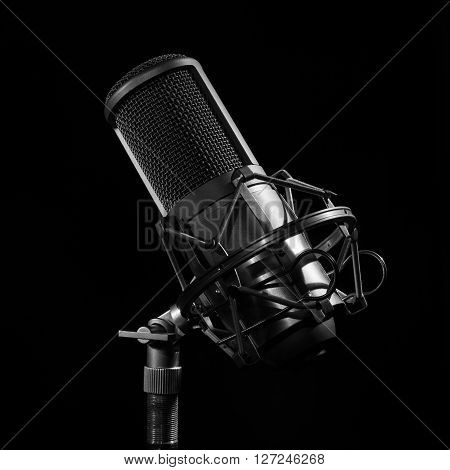 Professional Studio Microphone on black background. light brush