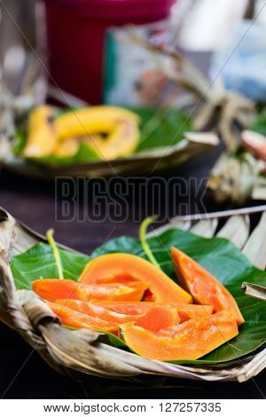 Close up of slices of sweet papaya served on weaved platter