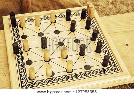 Wooden brain board game. Leisure game. Alquerque board game.