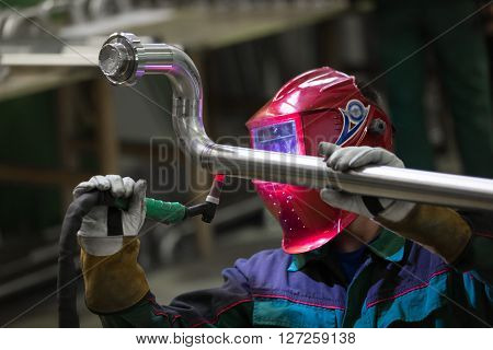 Industrial worker with protective mask welding inox elements in steel structures manufacture workshop. poster