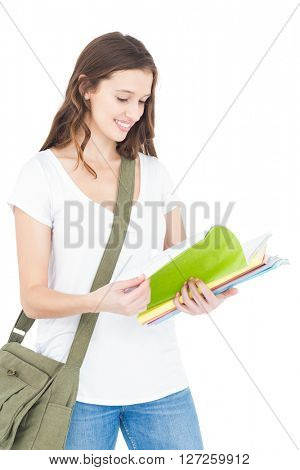 Happy female college student studying while standing on white background