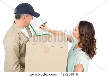 Female customer signing on paper with delivery man standing on white background