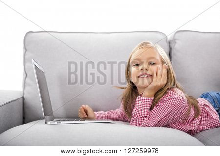 Happy little girl at home working with a laptop