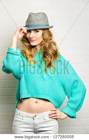 Cheerful pretty woman in a bright casual sweater and a felt hat. Beauty, fashion. Bright make-up, cosmetics.