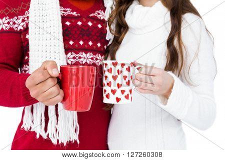 Happy couple with santa hats holding mug on white background