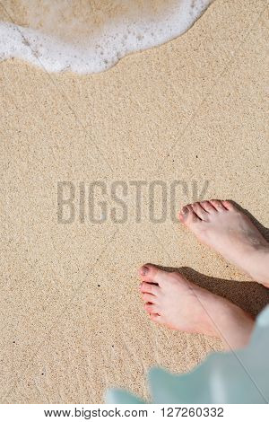 Close up of young woman feet on a tropical sandy beach