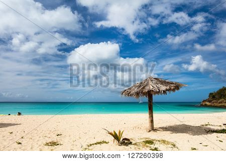 Idyllic tropical Ffryes beach with white sand, turquoise ocean water and blue sky at Antigua island in Caribbean