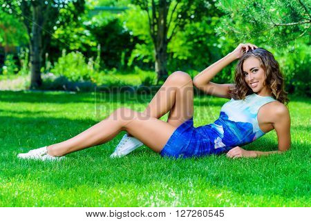 Happy beautiful girl in bright summer dress lying on a green lawn in the summer park. Beauty, fashion. Holidays.