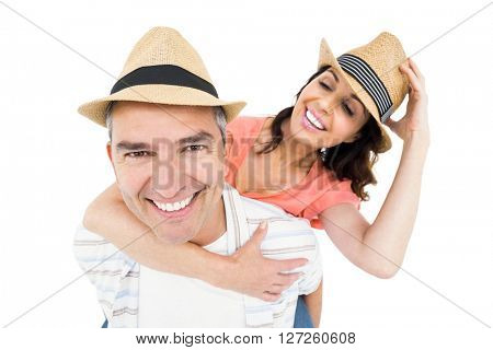 Handsome man piggy backing his wife against white background