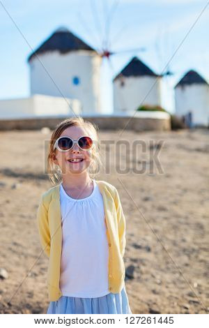 Cute little girl in front of windmills at popular tourist area on Mykonos island, Greece