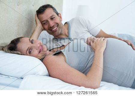 Expecting couple lying on bed and chatting in their bedroom