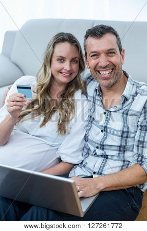 Expecting couple sitting on floor and using laptop