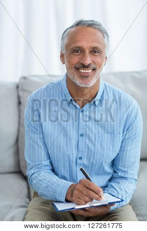 Portrait of man sitting with a clipboard on sofa