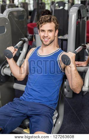 Fit man using weight machine at gym