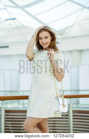 Beautiful young woman in white dress in the shop
