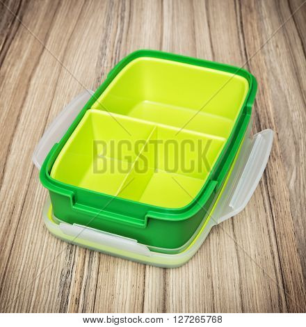 Green plastic box for food storage on the wooden background. Kitchen utensil. Close up photo.