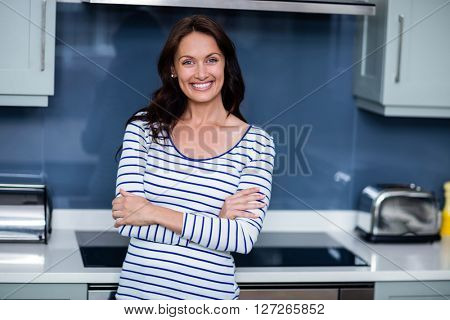 Portrait of happy young woman with arms crossed while standing in kitchen
