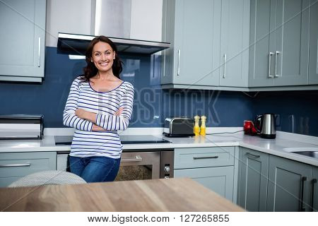 Portrait of smiling young woman with arms crossed while standing in kitchen