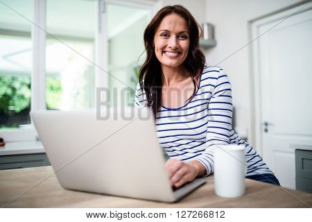 Portrait of happy woman working on laptop while holding coffee mug at table in kitchen