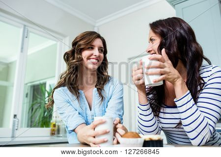 Smiling friends holding coffee mugs at table in kitchen