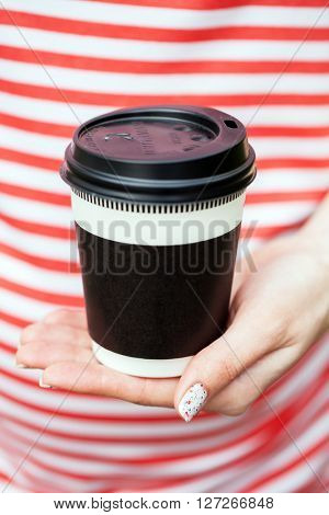 a girl sits with the cup of coffee in a park