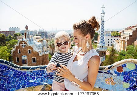 Happy Mother And Baby Checking Photos In Camera At Park Guell