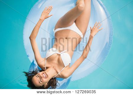 High angle view of beautiful woman relaxing on inflatable ring at swimming pool